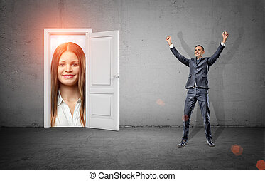 A happy businessman in victory motion stands in a room with...