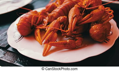 Freshly baked red crawfish on white plate on a table in a...