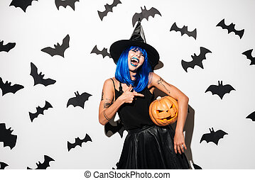 Amazing young woman in witch halloween costume - Photo of...
