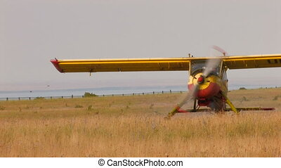 plane with propeller stands in the middle of the field,...