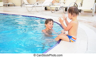 two boys brother bathe in the swimming pool at the resort...