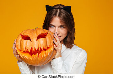 Serious young woman dressed in crazy cat halloween costume -...