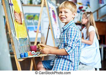 Smiling Little Boy in Art Class - Side view portrait of...