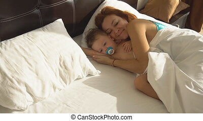 mom with baby son awake in the morning in the bedroom of the...