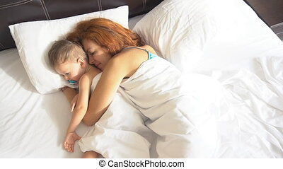 mother and little boy awake in the morning in hotel - mother...