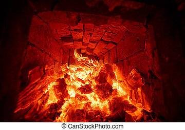 The firewood burning in the fire of the furnace. - The wood...
