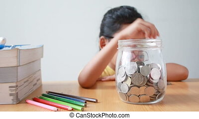 Asian little girl putting the coin into a clear glass jar...