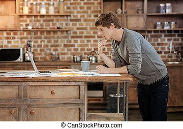 Young man reading article on laptop in the kitchen -...