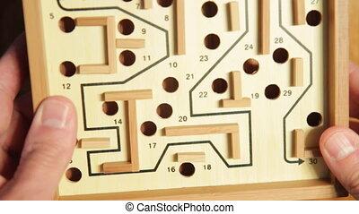 Guiding a ball through a maze. - Carefully guiding a steel...