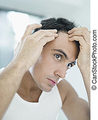 male beauty - caucasian adult man checking hairline Vertical...