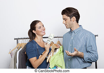 Female holds money in front of surprised man at clothing store