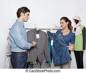 Couple comparing clothes in clothing store - Young man and...