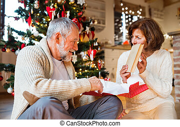Senior couple in front of Christmas tree with presents. -...