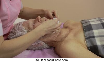 Beautician removing cream from woman's face - Hands of...