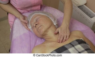 Senior lady enjoying massage in beauty salon - Top view of...