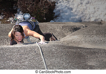 Focused - A strong woman struggles up a steep rock face in...