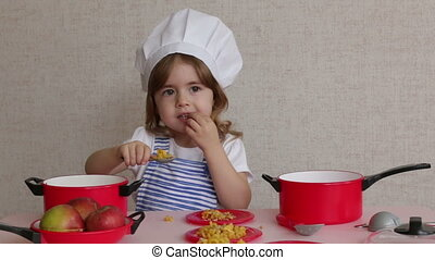 Portrait Adorable little girl in chef hat cook food -...