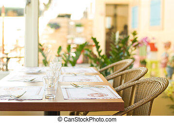 Tableware on table with series chairs. Restaurant in...