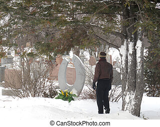 Man at cemetary in winter - Man looking at gravestone with...