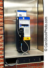 Public payphone in stainless steel phone booth on red brick...