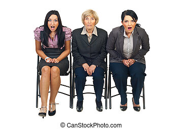 Shocked group of businesswomen sitting on chair at...