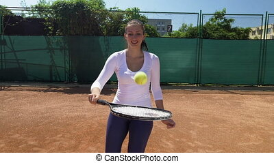 Joyful girl balancing ball on tennis racket at tennis court