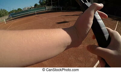 POV hands of tennis player holding racket and hitting ball...