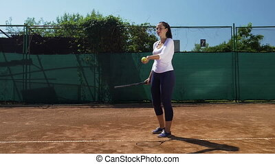 Young woman hits the tennis ball with racket at tennis court