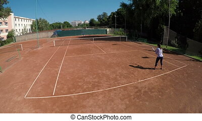 Two women play tennis outdoors at tennis arena