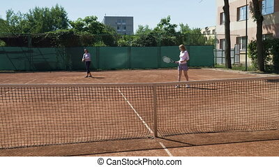 Two girl friends playing doubles tennis match winning and...