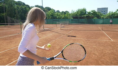 Two friends play tennis together on the field