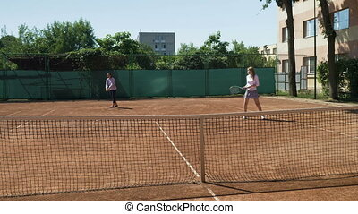 Two tennis players playing double at tennis court