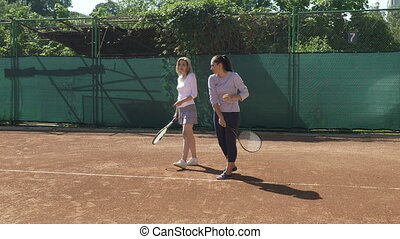 Young woman takes tennis classes and learns how to hold...