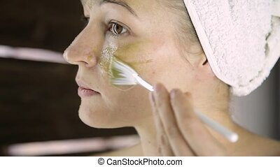 Beautiful woman in towel applying green clay mud mask to her...