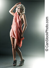 Young slim sexy woman covered by red cloth with backlights