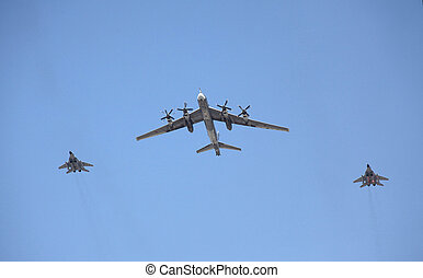 strategic bomber flies with two fighters - The strategic...