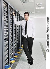 young engeneer in datacenter server room - young handsome...