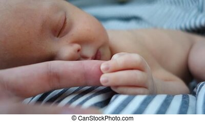 Newborn baby sleeping keeps mum by the finger close-up -...
