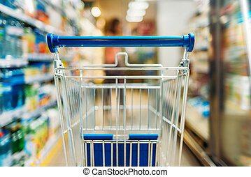 empty shopping cart in supermarket - close up view of empty...