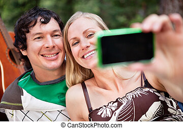 Young cheerful couple photographing themselves