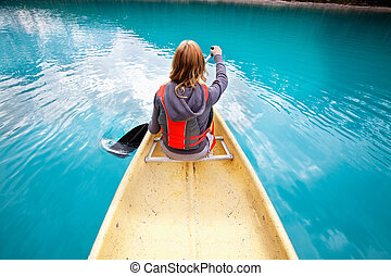 Woman rowing boat - Rear view of woman rowing boat on calm...