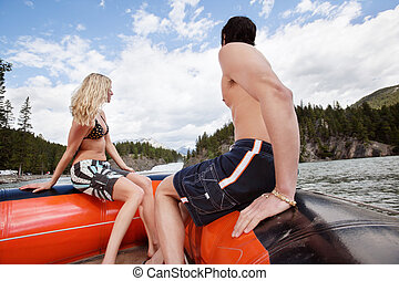 Young couple in raft looking at view under cloudy sky