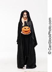 Full length portrait of a dreadful woman in halloween...