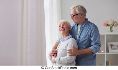 happy senior couple looking through window at home -...