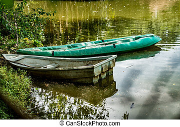 Old plastic boat in the green lake