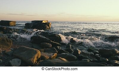 Slow motion two huge stones in the water on a stony bank -...