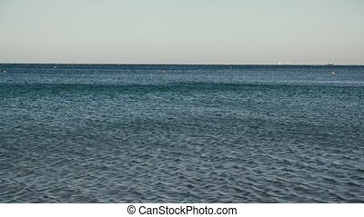 Sea blue sea with ships on the horizon - Sea ripples from...