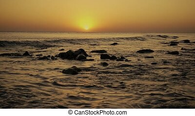 Slow mo the wave rolls over a stony shore at sunset - Slow...