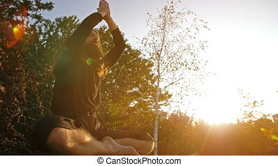 Yogi pray on sunset - Yogi sitting in meditation on the rock