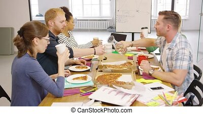 People eating in office - Group of young people in casual...
